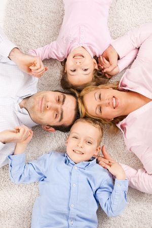 Portrait of happy family lying on carpet with their heads close together, smiling. photo