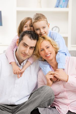 Happy family at home with daugther and son, smiling. Children hugging their parents from behind photo