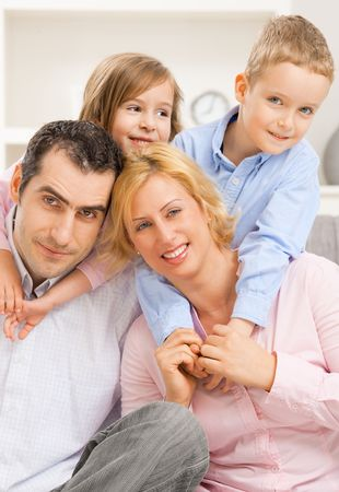 relatives: Portrait of happy family, children embracing their parents from behind. Stock Photo