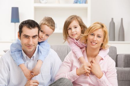 Happy family at home, children embracing their parents. Stock Photo - 5100997