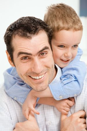 Closeup portrait of happy father holding his son on his back, smiling. photo