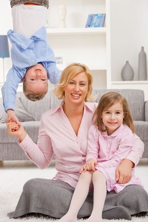 Family fun. Mother holding her daughter on knees, boy hangging upside down. photo