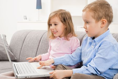 Happy children sitting on couch at home, browsing internet on laptop computer, looking at screen smiling. photo