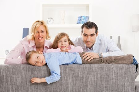 Portrait of happy couple and their two children at home, smiling. Stock Photo - 5024738