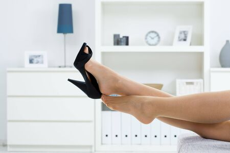 female feet: Woman legs in stockings, taking off high heel shoes. Stock Photo