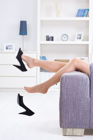 female soles: Woman legs in stockings, taking off high heel shoes. Stock Photo