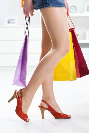 the sole of the shoe: Long female legs in stockings. Hands holding colorful shopping bags.