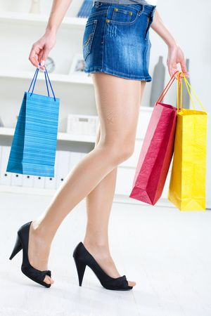 Long female legs in stockings. Hands holding colorful shopping bags. photo