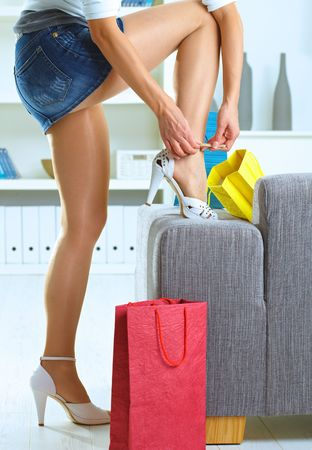 Long female legs in stockings. Woman taking off shoes after shopping at home.  photo