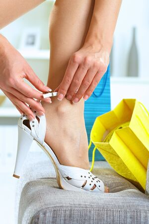 Closeup photo of female leg and hands. Woman fitting her high heel shoe. photo