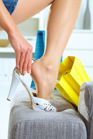 Closeup photo of female leg and hands. Woman fitting her high heel shoe. Stock Photo - 5041665