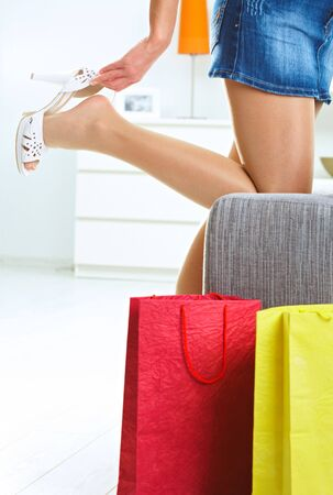 Woman taking off high heel shoe at home. Colorful shopping bags in front. photo