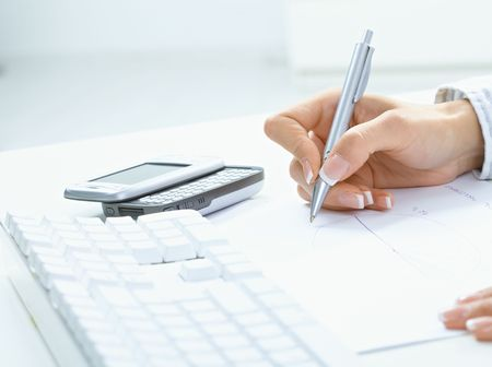 adult  body writing: Female hand holding pen, writing on paper, beside desktop computer keyboard and mobile phone.