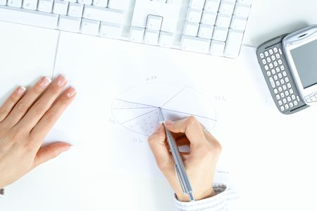 Female hand holding pen, drawing pie chart, beside desktop computer keyboard and mobile phone. photo