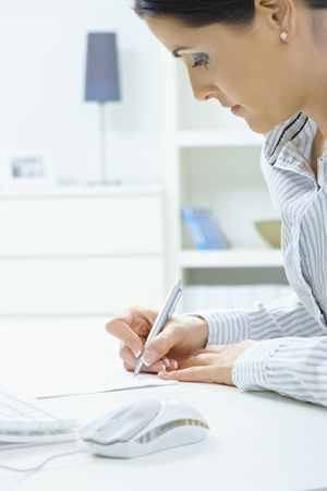 adult  body writing: Closeup portrait of young woman writing with pen on paper, focus on hands.