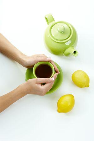 high angle shot: Female hands holding tea cup on table, along with green jug and lemones. High angle shot. Stock Photo