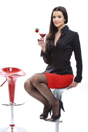 temptations: Sexy young woman sitting on bar chair, holding glass of cocktail in hand.