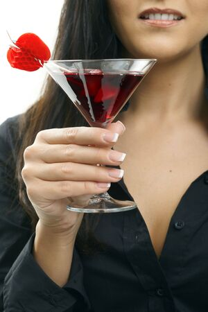 Partially visible young woman holding glass of cocktail. Selective focus on hand. photo