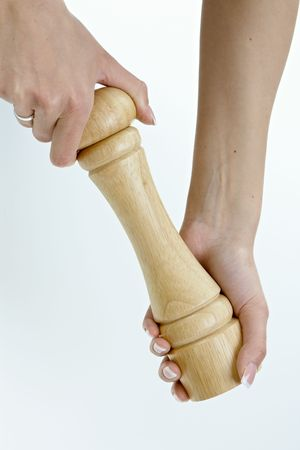 Femal hands holding pepper grinder. Isolated on white. photo