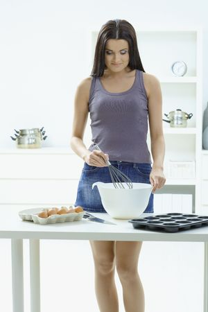 Young woman standing at kitchen table, whisking eggs in a bowl, smiling. photo