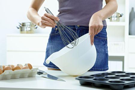 Female hands whipping eggs in bowl, using egg whisk. photo
