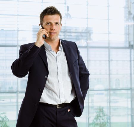 handy: Businessman talking on mobile phone in front of office window. Stock Photo