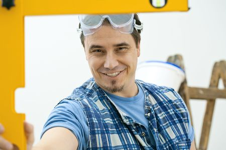 Worker measuring with square level tool, smiling. Isolated on white background. photo