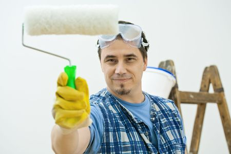 Worker painting with roller, isolated on white background. photo