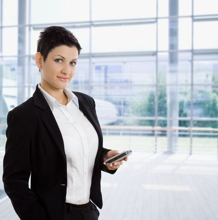 Young businesswoman standing at office lobby using mobile phone, smiling. photo