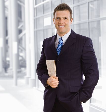 Portrait of smiling businessman, holding newspaper, standing in lobby of corporate building. photo