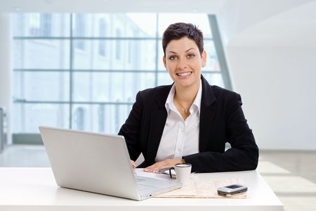 open collar: Happy young businesswoman sitting at office desk, working with laptop computer, smiling.