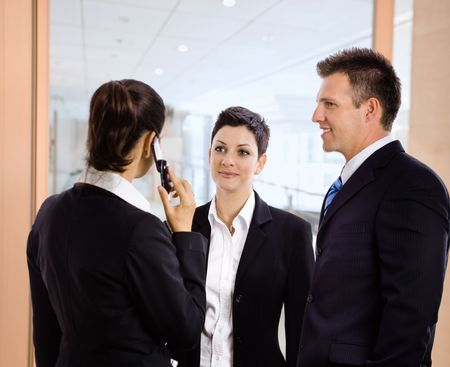 Business team standing in office hallway, businesswoman talking on mobile phone. Stock Photo - 5100998