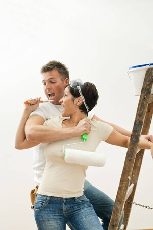 Young couple embracing and having fun while painting their new home. photo