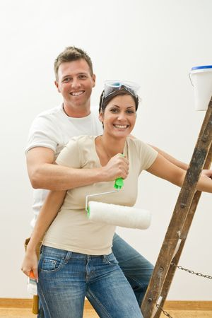 Happy couple hugging and smiling, while improving their new home. photo