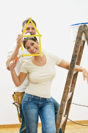 Happy young couple playing with ruler during home improvement. photo