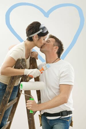 decoration work: Young couple painting new home. Standing on ladder, kissing. Isolated on white background.