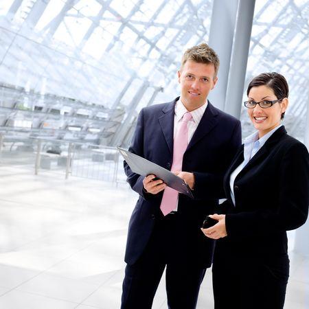 jovenes empresarios: Feliz la gente de negocios hablando en la oficina vest�bulo, sonriendo. Foto de archivo