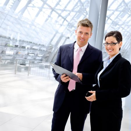color consultant: Happy business people talking at office lobby, smiling. Stock Photo