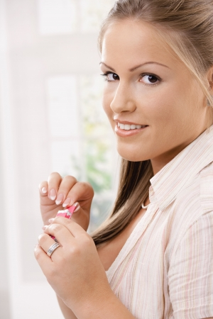 Closeup portrait of happy young woman holding chewing gums in her hand. photo