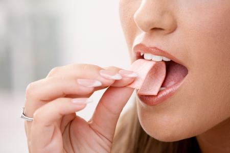 goma de mascar: De cerca los detalles de la mujer puesta rosa chicle en la boca.