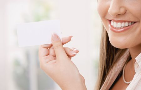 Partially visible young woman with withe teeth holding an blank white card with copy space. Selective focus on card. photo