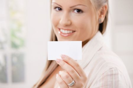 Beautiful young woman showink a blank white business card with copy space. Selective focus on card. photo