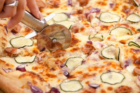 Humand hand cutting pizza slices with pizza cutter. photo