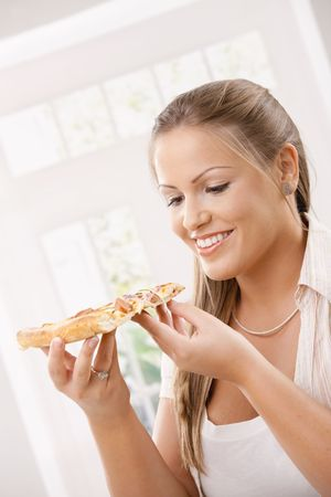 Beautiful young woman holding pizza slice, smiling. photo
