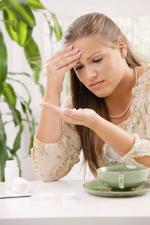 Young woman having headache, holding her head and looking at pills in hand. photo