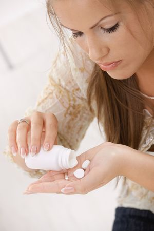 Closeup of young woman girl taking pills from bottle. Stock Photo - 5071131