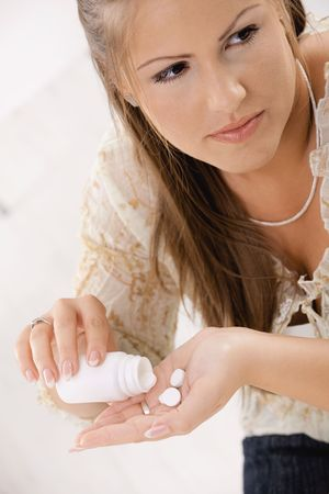 Closeup of young woman girl taking pills from bottle. Stock Photo - 5071083