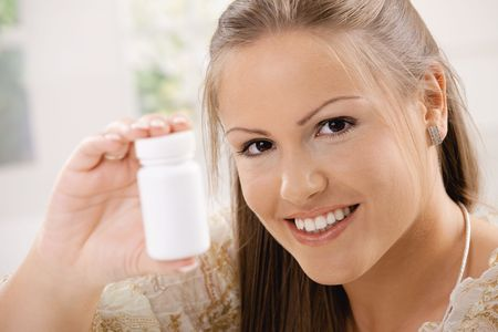 Beautiful young woman showing white pill bottle, copy space. Stock Photo - 5071086