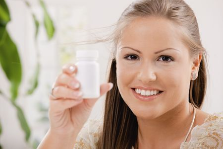 Beautiful young woman showing white pill bottle, copy space. photo