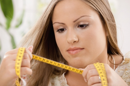 'tape measure': Young woman on diet looking at tape measure.